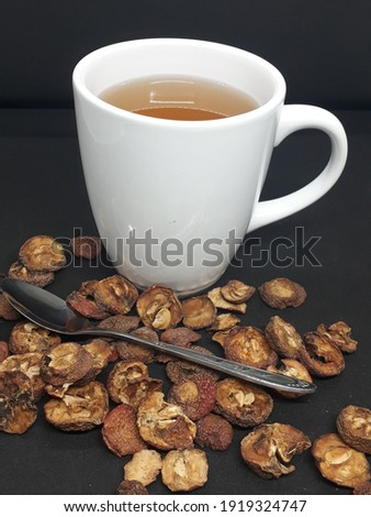 a white cup of freshly brewed sweet haw flakes tea with stainless steel stirring spoon and dried haw flakes fruit Stock photo ©