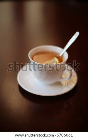 A white cup of tea with lemon on a table. Shallow DOF.