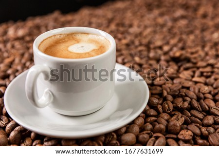 A white cup with aromatic coffee stands on scattered grains. Close-up.