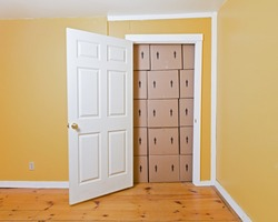 A white door opens in a yellow room to reveal a room full of brown cardboard boxes.