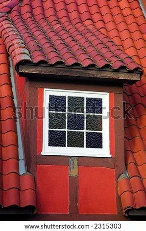 A white dormer window in a red Danish building with a tiled roof.