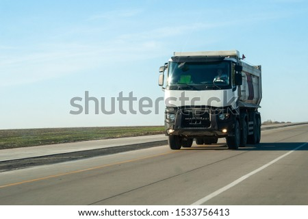 A white dump truck drives out of town on a flat asphalt road among fields against a blue sky on a sunny day. A machine for transporting building materials rides on the highway #1533756413