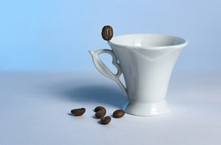 A white elegant coffee cup with a coffee grain on its edge and five scattered at its base on a light blue background with a selective focus