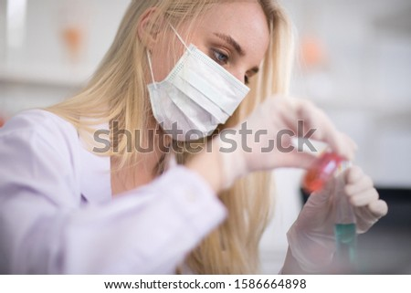 A white female scientist wearing a mask While doing research in the laboratory