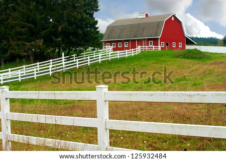 A white fence leading up to a big red barn
