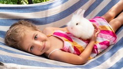 A white fluffy bunny in the arms of a cute girl. The child holds a decorative rabbit in his arms and rides on a hammock on a sunny day. Happy little girl with positive emotions smiles at her pet.