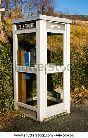 a white french phone booth in a rural surrounding