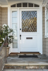 A white front door to a beige home, with an intricate, diagonal paned window. Also seen is a stone porch and stairs, railing, and a plant.