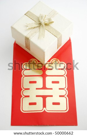 A white gift or jewelry box with a red Chinese double happiness packet.