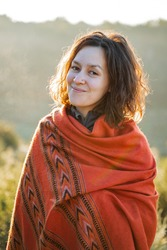 a white girl wrapped in a blanket enjoys life in the morning sun, orange plaid with an ethnic pattern, curly hair, peace and nature, against the background of the forest