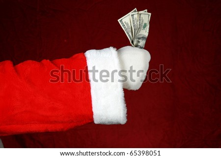A white gloved santa arm holds a fist full of cash against a crushed red velvet background