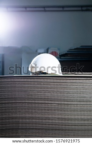 A white hard hat on a pile of cartons, side view.