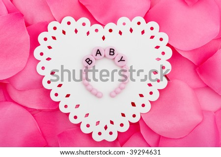 A white heart  cut out sitting on a pink flower petal background, love heart