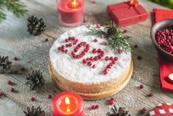A white holiday mousse cake covered with coconut flakes, imitating snow. On the cake, the number 2021 is put out in red berries. The concept of a New year.