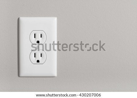 A white home electrical outlet on a light grey wall. Foto stock ©