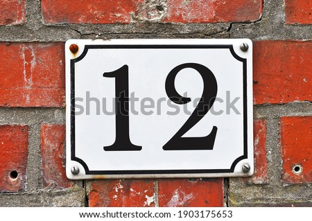 A white house number plaque, showing the number twelve (12) Stock photo ©