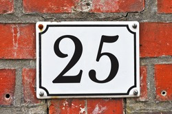 A white house number plaque, showing the number twenty five (25)