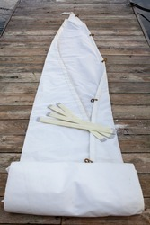 A white jib sail rolled up on the dock with battens and copper hanks sewn on.