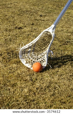 a white lacrosse stick scooping the ball off the ground