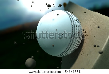 A white leather stitched cricket ball hitting a wooden cricket bat with dirt particles emanating from the impact at night