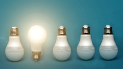 A white light bulb glows among the others. concept ideas. stands out among others. a bright lamp shines