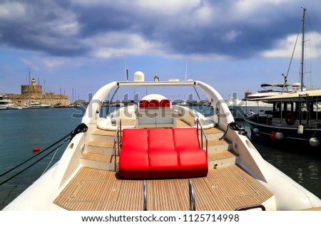 A white luxurious boat with red leather seats stands at the pier in the sea  port  Rhodes, Greece - - the best Island for excursions, travel, recreation and vacation.\n