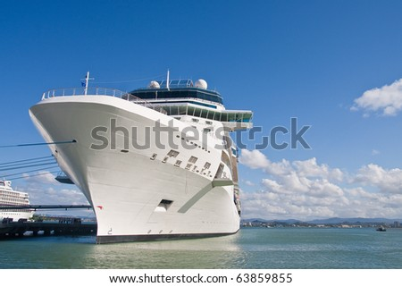 A white luxury cruise ship tied to a pier under blue skies on calm water