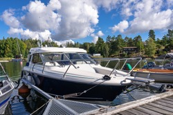 A white luxury yacht is moored at the pier in marina on a summer day. Wooden jetty pier berth. Parking for yachts and boats. Yachting equipment. People lifestyle. The Stockholm archipelago in Sweden.