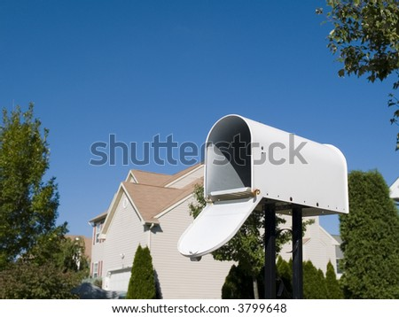 A white mailbox against a fresh blue sky, with an upscale house in the background.