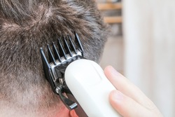 A white male during a fresh shaved hair cut with electric clippers and foils at home in the bathroom.