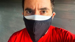 A white male wearing double protective masks against covid 19 looks at the camera against a seamless background