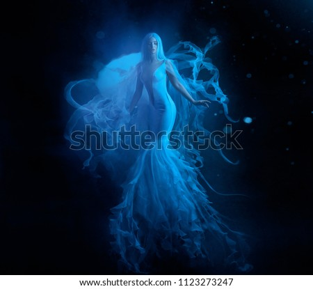 A white mermaid, with very long and blue hair floating under the water. An unusual image, the tail of a jellyfish. Levitation and weightlessness. Pale skin, gentle makeup. Art photo #1123273247
