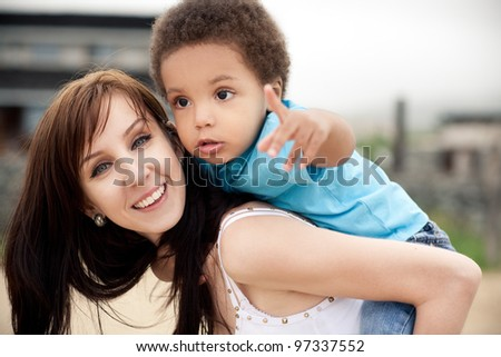 A white mother with a son of an african descend relaxing together outdoor.