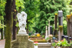 A white mourning porcelain angel on a cross in Mirogoj cemetery, Zagreb, Croatia