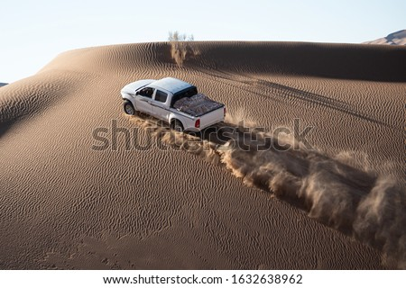 a white pickup truck is going up from a sand dune and splashing sands on air and around with sand textures on sand dune in dasht e lut desert. car traveling in desert and climbing a sand dune