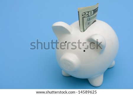 A white piggy bank on a blue background with copy space