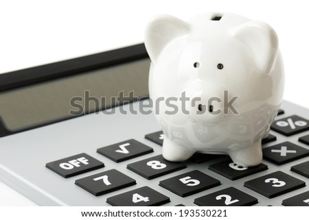 a white piggy bank on top of a calculator