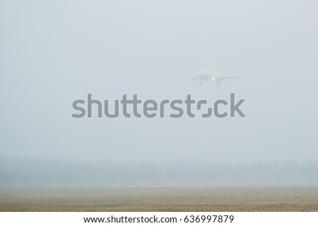 A white plane is landing on a runway during a foggy day