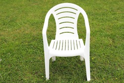 A white plastic chair stands on a green lawn background in the village. Self-isolation. Loneliness. Social distancing. Coronavirus pandemic.