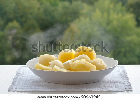 A white plate of boiled potatoes. The boiled potatoes. Potatoes couple. Plate on a white napkin. Green background ストックフォト ©