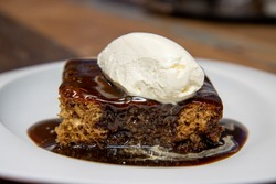 A white plate of delicious sticky toffee pudding chocolate cake with cream and chocolate sauce on a wooden kitchen work top