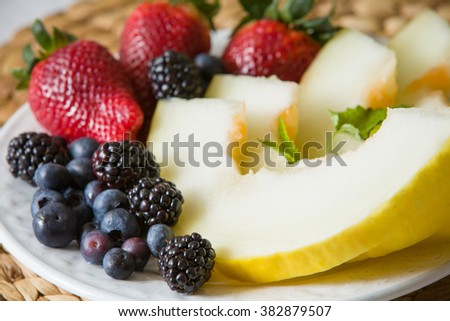 A white plate with fresh organic fruit. Summer snack. Blueberries, melon, strawberries with mint. Healthy food for healthy life.
