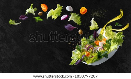 A white plate with salad and floating in the air ingredients: olives, lettuce, onion, tomato, mozzarella cheese, parsley, basil and olive oil. Black background. Copy space.