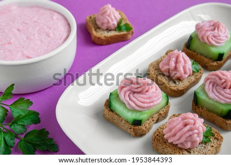 A white plate with taramasalata crostini and a white bowl with tarama on the purple background close-up Stok fotoğraf ©