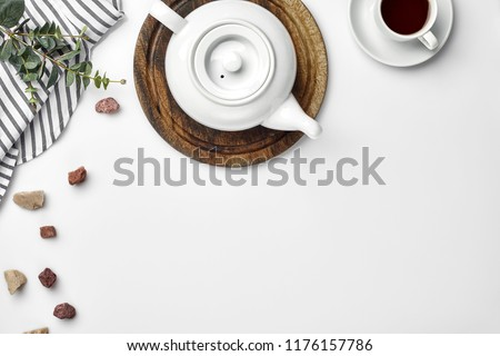 A white porcelain teapot on a wooden board and a white cup with tea on a table. Top view. Copy space.