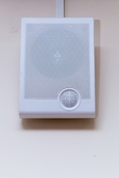 A white radio transmitter hangs on a beige wall. On the front side there is a grill with small holes for a loudspeaker. Electronic device for listening to messages, music and news.