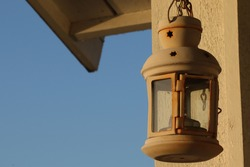 A white rusty rustic candle lantern hanging from a chain lit by sunrise