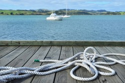 A white sailing rope lying on a wharf pier waterfront causeway in Taipa Mangonui in Northland North Island of New Zealand against landscape view of sailing boats in the background.
