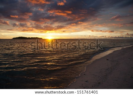 A white sand beach on Gangga Island, just north of the island of Sulawesi in Indonesia, is lit by the last light of day.  This region is known for its high marine biodiversity. #151761401