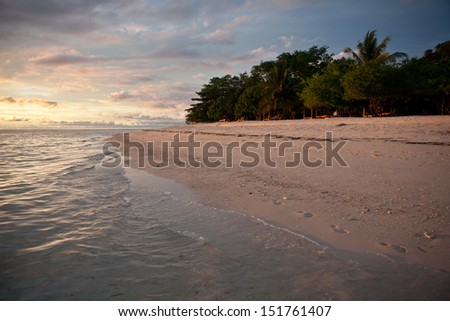 A white sand beach on Gangga Island, just north of the island of Sulawesi in Indonesia, is lit by the last light of day.  This region is known for its high marine biodiversity. #151761407